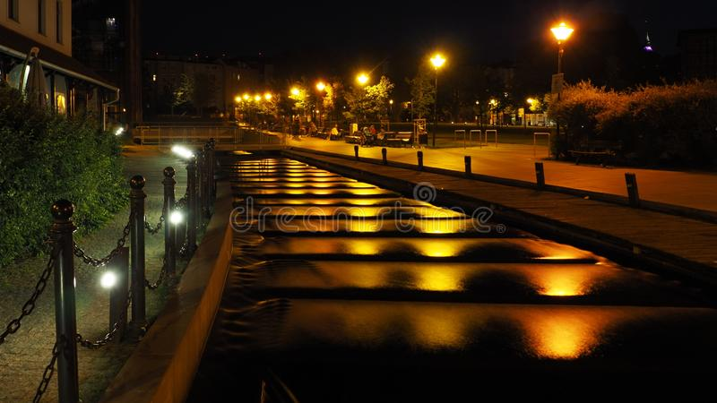 Night view of the river flowing down the stairs on the Mill Island in Bydgoszcz, Poland. Night view of the river flowing down the stairs reflecting the yellow stock image