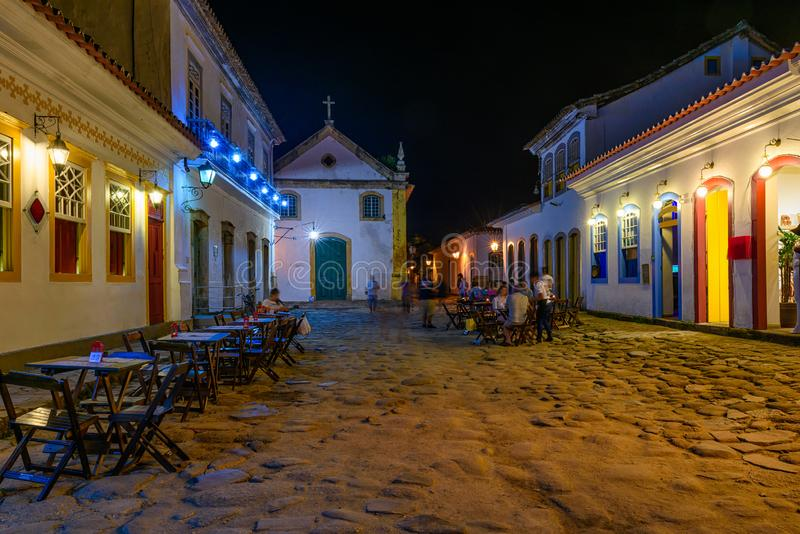 Night view of street of historical center with tables of restaurant in Paraty, Rio de Janeiro, Brazil. Paraty is a preserved Portuguese colonial and Brazilian royalty free stock photography