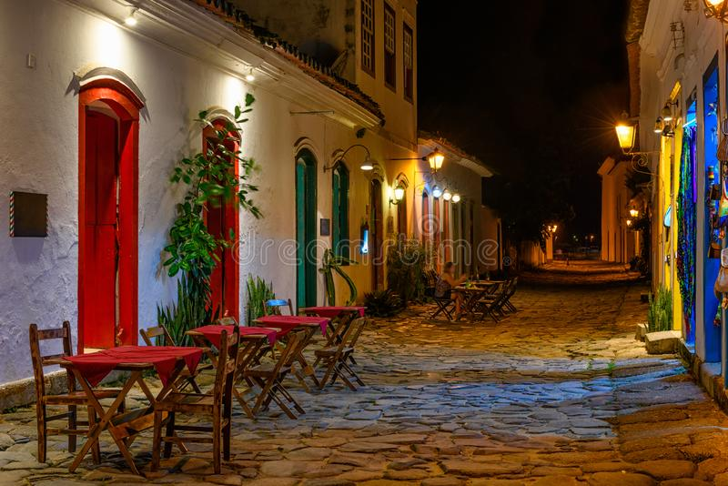 Night view of street of historical center with tables of restaurant in Paraty, Rio de Janeiro, Brazil. Paraty is a preserved Portuguese colonial and Brazilian stock photography