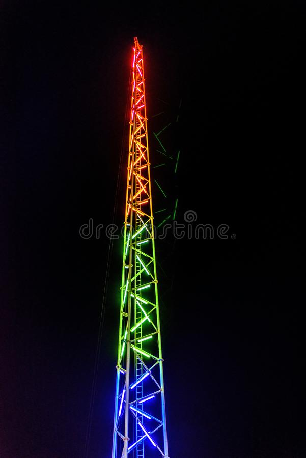 Night view to Reverse bungee fairground ride tower. Colorful lights glowing. Ayia Napa, Cyprus stock images