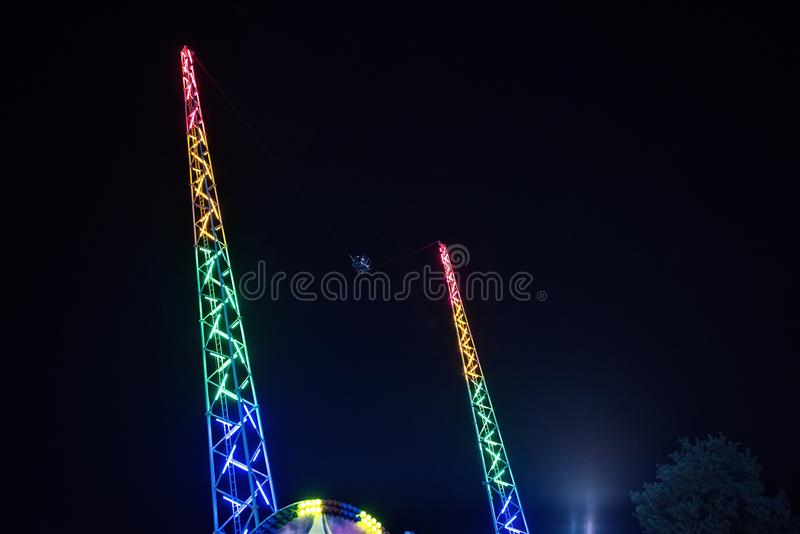 Night view to Reverse bungee fairground ride towers. Colorful lights glowing. Ayia Napa, Cyprus royalty free stock image