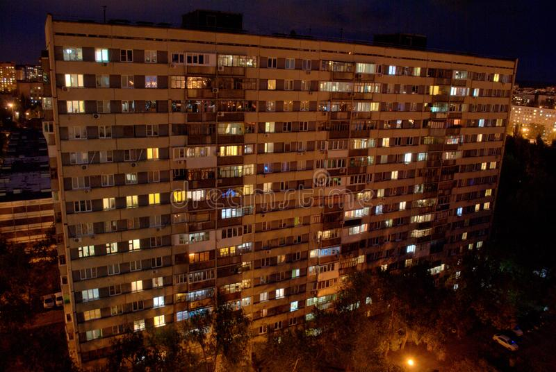 Night view of the two-storied 16-storey residential building with many glowing windows in the city of Togliatti. Night view of the two-storied 16-storey stock photos