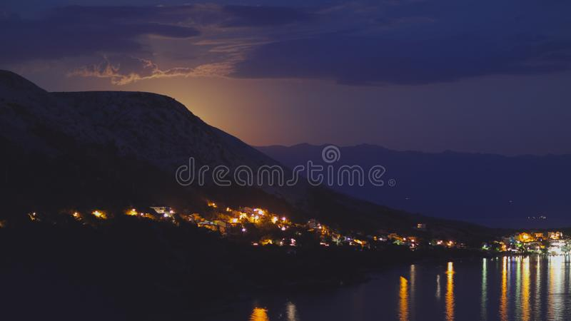 Night view under the moon light onto the city on a shore of Adriatic sea from the rocky hill in Croatia, different color tones royalty free stock photo