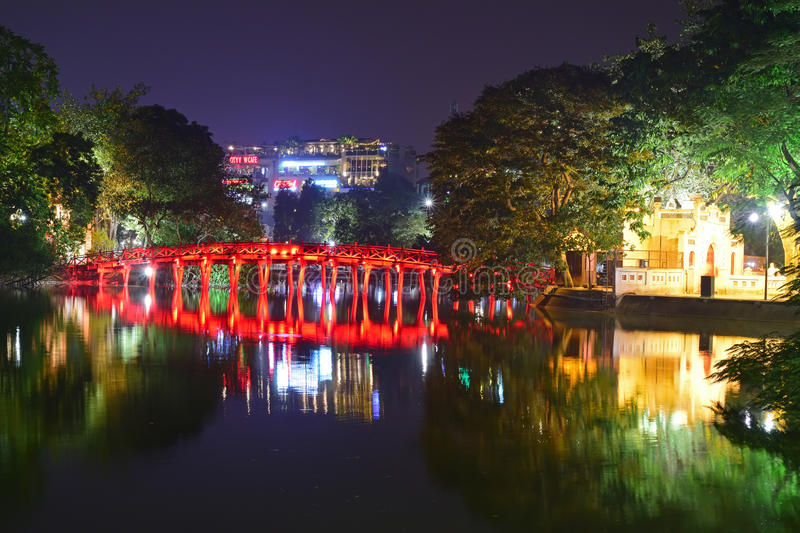 Night view with water reflection of The Huc Bridge in bright red with entry building of Ngoc Son Temple, Hanoi, Vietnam. The bridge name means Morning Sunlight royalty free stock image