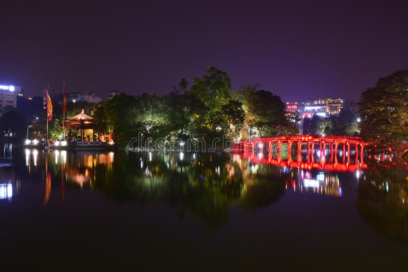 Night view with water reflection of The Huc Bridge in bright red with Ngoc Son Temple, Hanoi, Vietnam. The bridge name means Morning Sunlight Bridge connecting royalty free stock photo