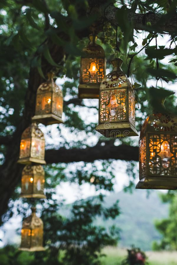 Night wedding ceremony with a lot vintage lamps and candles on big tree royalty free stock photography