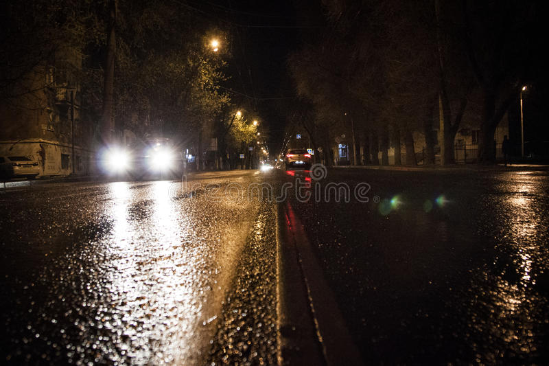 Night wet road in the rain. Wet from the rain asphalt lights the lights of a passing car in the night. Dividing strip, Wet road royalty free stock images