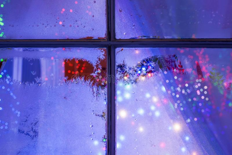 The night window with frosty patterns and bright multicolored Christmas. New Year`s lights and decorations outside the window. stock photo
