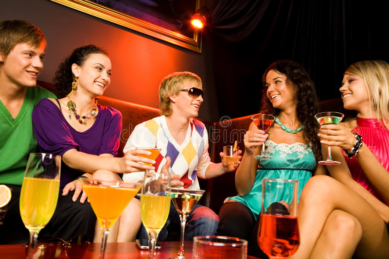 In the nightclub. Portrait of friends sitting on the sofa and holding the cocktails in the nightclub royalty free stock images