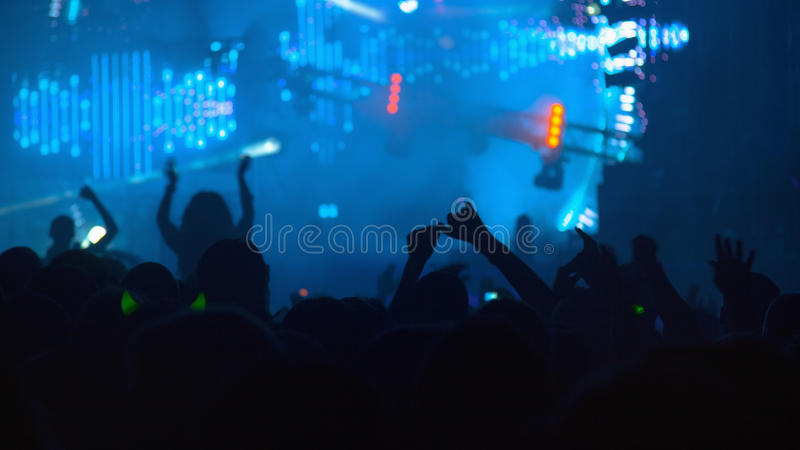Nightclub. Crowd in front of stage-lights raising hands in nightclub stock image