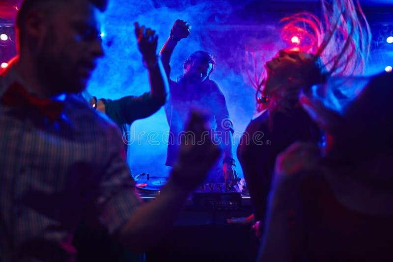 In nightclub. Disc jockey at the turntable in nightclub royalty free stock image