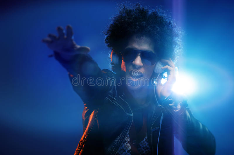 Nightclub dj. Cool club DJ gets the party started while listening to headphones and dancing in nightclub with afro and lens flare royalty free stock image