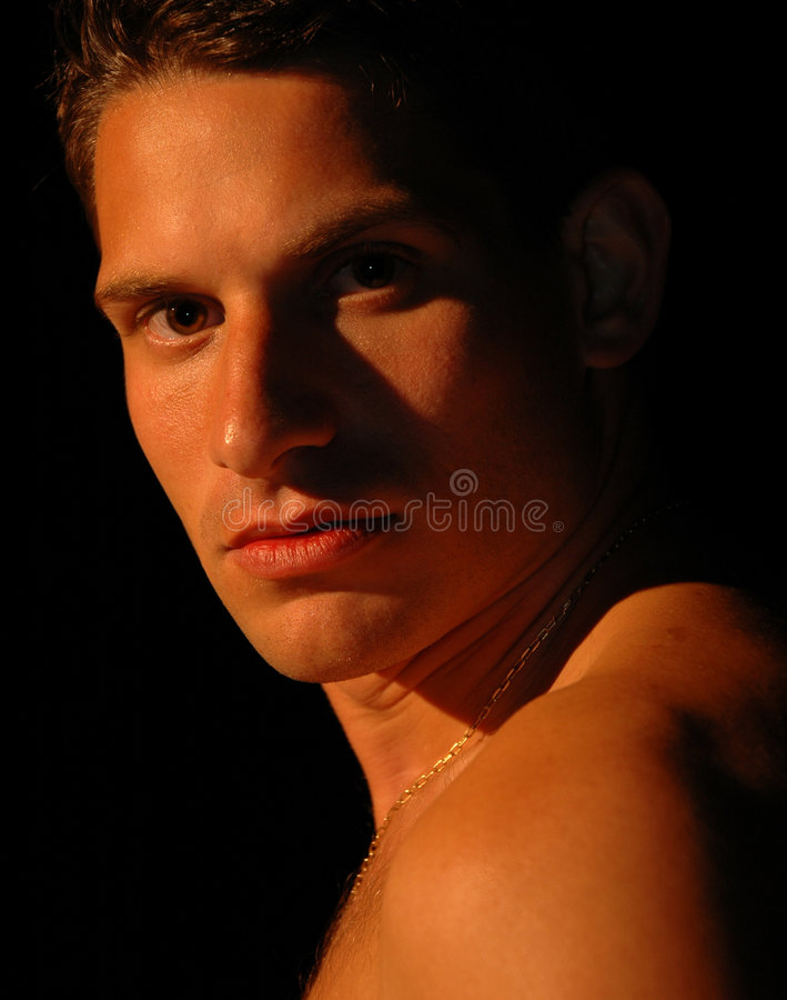 Nightfall. A handsome man in the final rays of light at nightfall stock photography