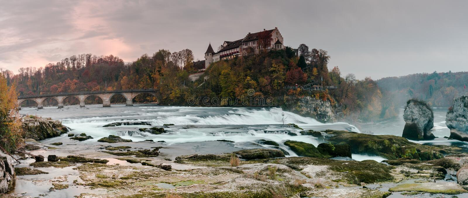 Nightfall and dusk on the Rhine Falls and Rhine River with an illuminated castle building on the water royalty free stock photo