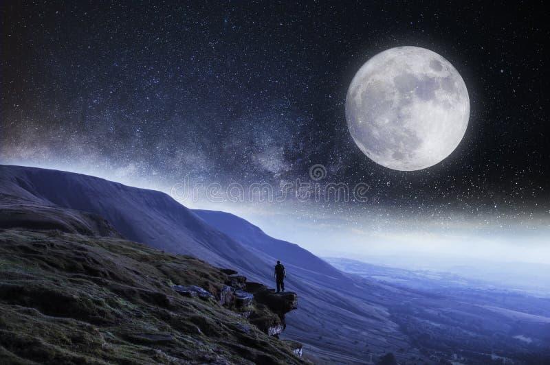 Nightime редактирует Hiker на краю скалы окруженной горами с луной и звездами выше стоковые изображения