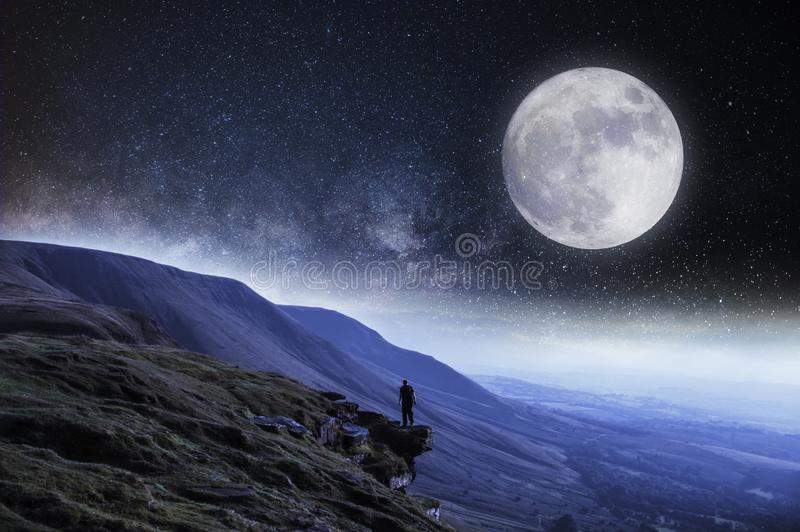 A nightime edit. A hiker on the edge of a cliff surrounded by mountains with the moon and stars above stock images