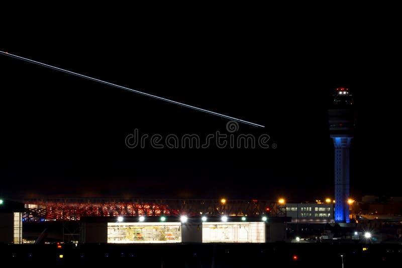 Nightimemening van de internationale luchthaven van Atlanta met luchtverkeerscontrole en stroken van vliegtuigen die over heldere stock foto