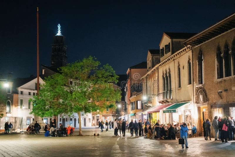 Nightlife in Campo San Polo square in Venice, Italy. Venice, Italy - May 10, 2019: Tourists and locals relax in Campo San Polo square with cafe and restaurant at royalty free stock photos