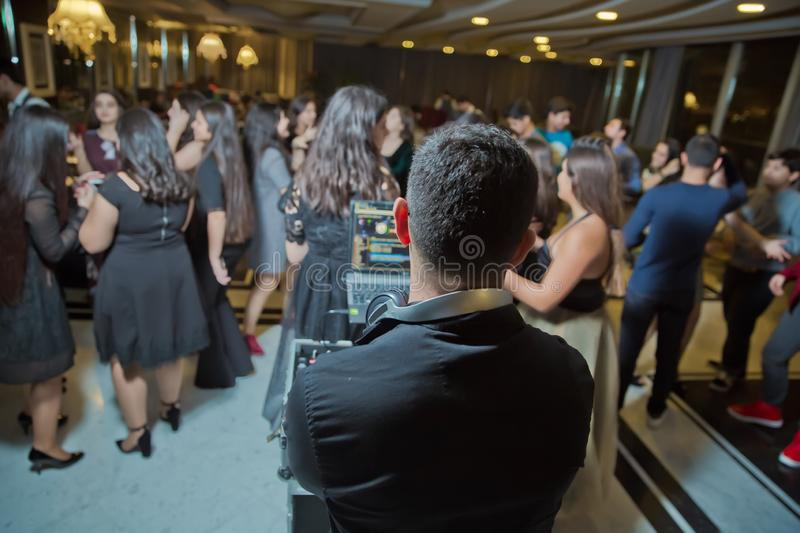 Nightlife concert concept. Dj stand back to the camera in front of the crowd of ladies and handsome mans dance in the dark, raised royalty free stock photography