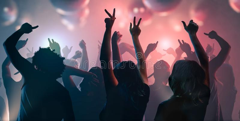 Nightlife and disco concept. Young people are dancing in club stock photo