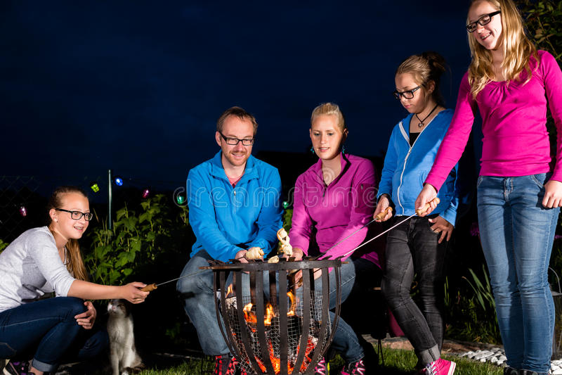 Nightly bbq party of family in their garden. They are grilling sausages on sticks in open fire stock image