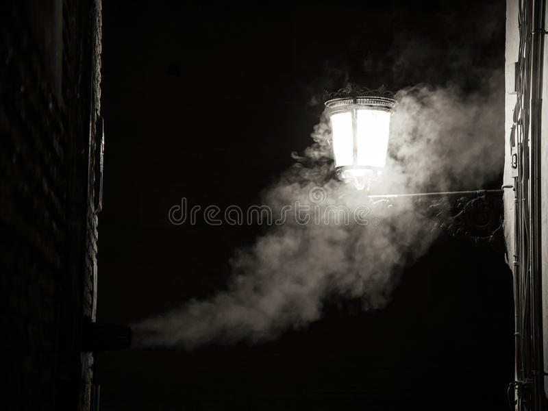 Nightly smoke. The smoke from a fireplace merges with the light of a street lamp during the night stock images