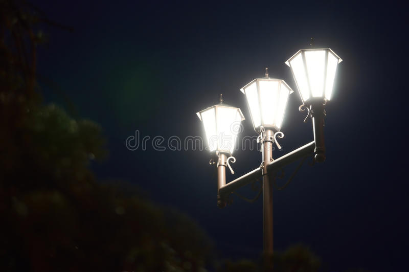 Nights lights. Of three lamps in the park stock photo