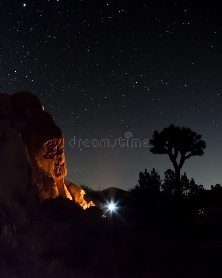 Nightscape av Joshua Tree National Park Camping - stjärnklar himmel och mjuk belysning på stenblocket arkivbild