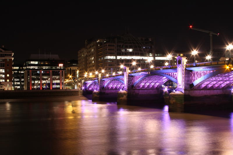 Nightscape with colored bridge. A view of an illuminated bridge and commercial waterfront buildings on the banks of the River Thames in London at night stock images