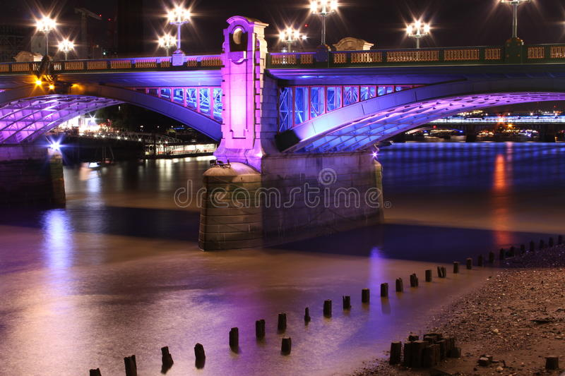 Nightscape with colored bridge. A view of an illuminated bridge and commercial waterfront buildings on the banks of the River Thames in London at night royalty free stock photography