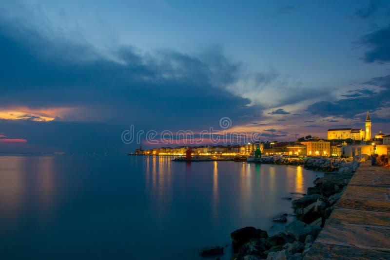 Nightscape pitoresco do litoral do mar de adriático com casas e o farol iluminados no crepúsculo, Piran, Eslovênia foto de stock