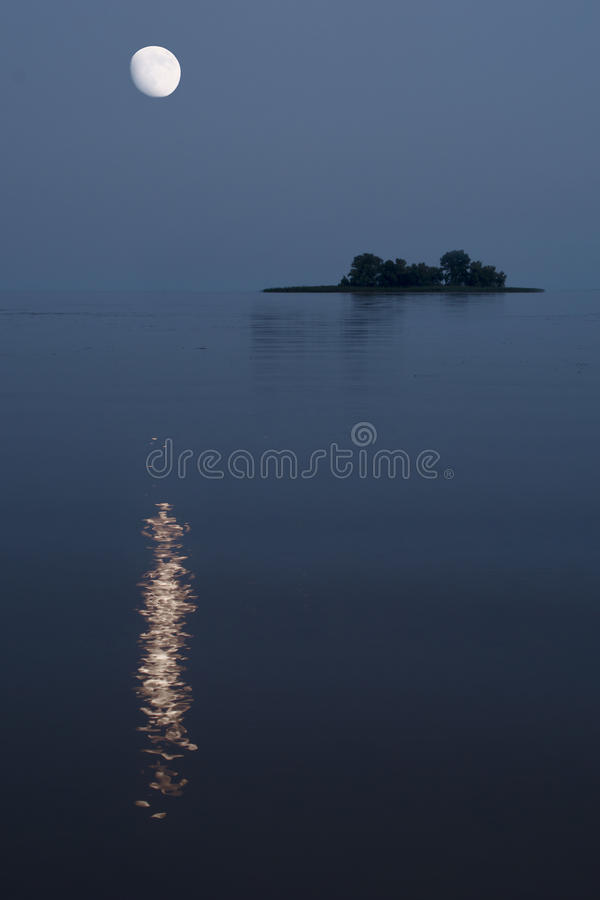 Nightscape van kalme rivier met heldere maan over klein eiland royalty-vrije stock foto's