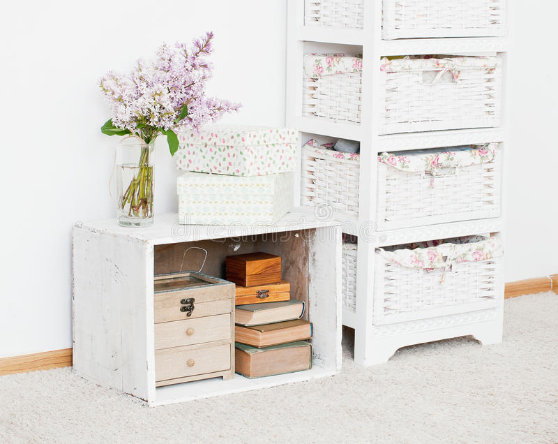 Nightstand with flowers, storage boxes and books stock image