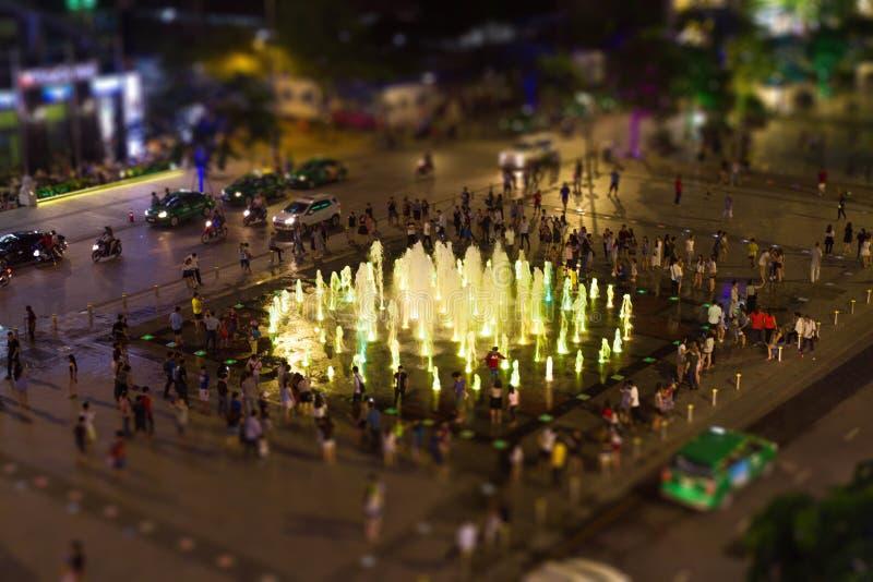 Фонтан окруженный людьми во время Nighttime стоковые изображения rf