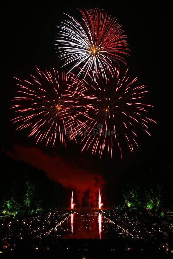 Красные и белые фейерверки разбросанные во время Nighttime стоковая фотография rf