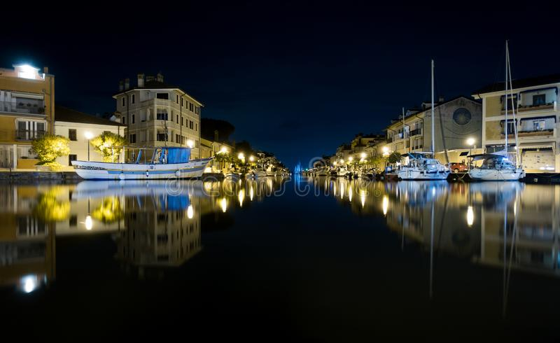 Nighttime shot of Port of Grado in Italy mirroring in water, with passageway to adriatic sea and thawed boats stock photography