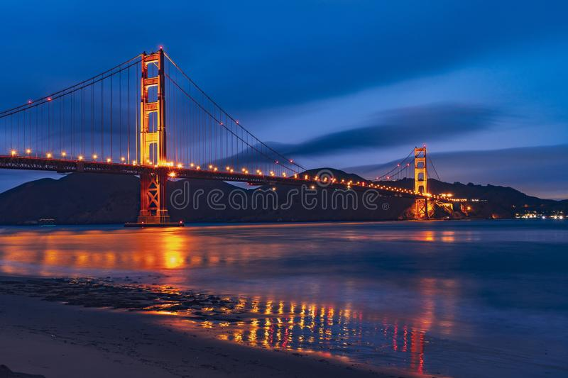 Nighttime view of Golden Gate Bridge reflected in the blurred water surface of San Francisco bay, dark blue sky background; stock photos