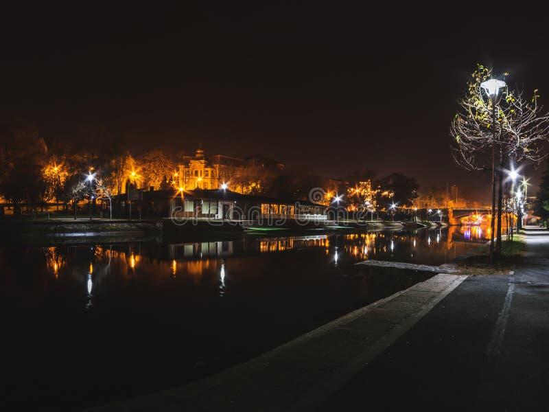 Nighttime w Timisoara parku rzeką z odbiciami i mostem fotografia stock