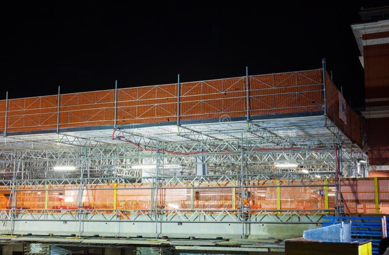 Nightview av material till byggnadsställningbeståndsdelar royaltyfri foto