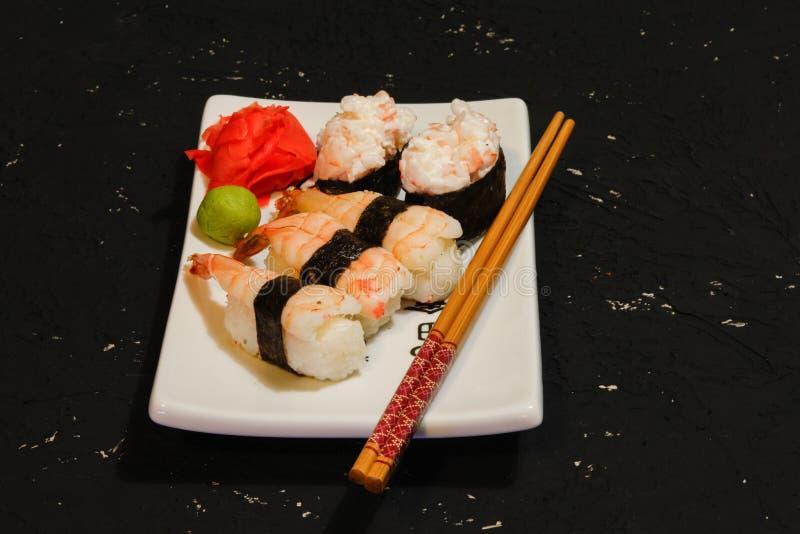 Nigiri寿司在黑背景的白色板材设置了 日本食物 亚洲鲜美晚餐 免版税库存照片