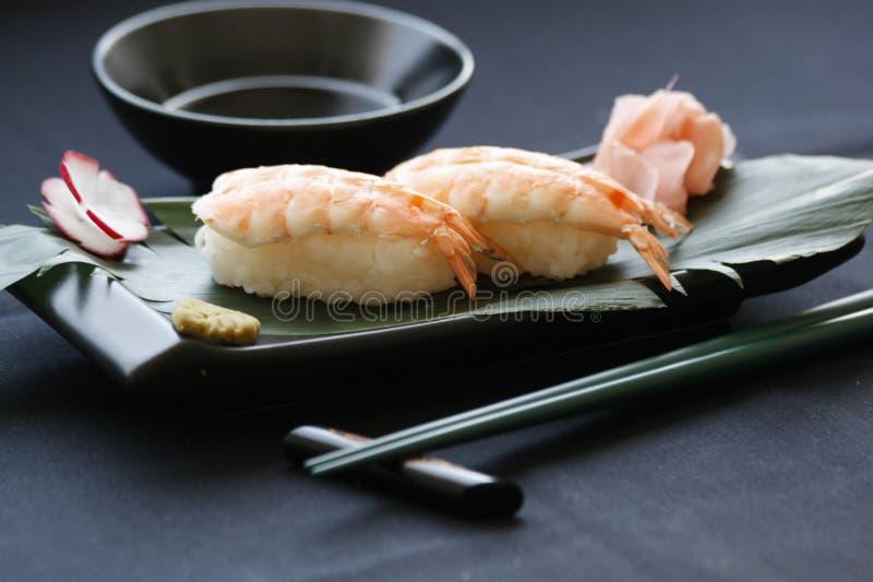 Nigiri寿司用虾和金枪鱼在一食家制地图在黑背景 库存照片