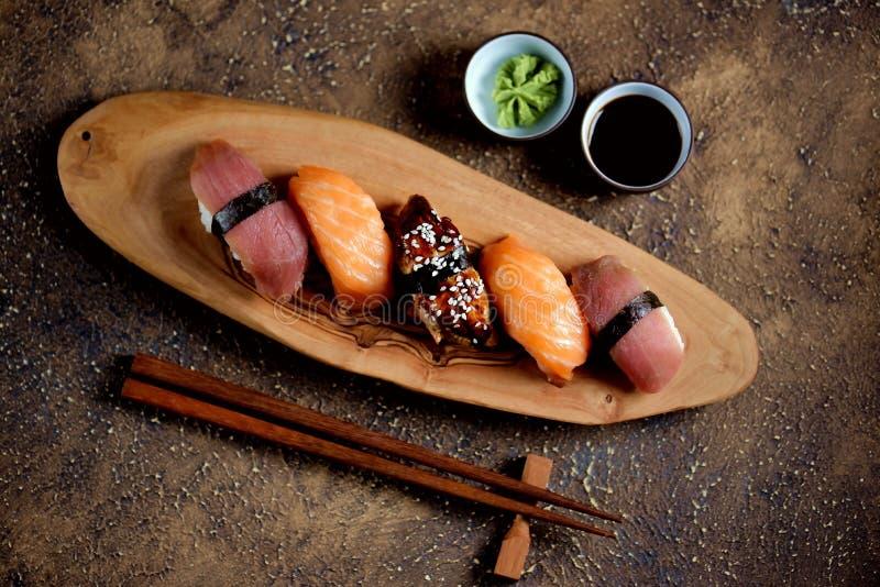 Nigiri dei sushi con il salmone fresco crudo, l'anguilla affumicata ed il tonno fotografie stock libere da diritti
