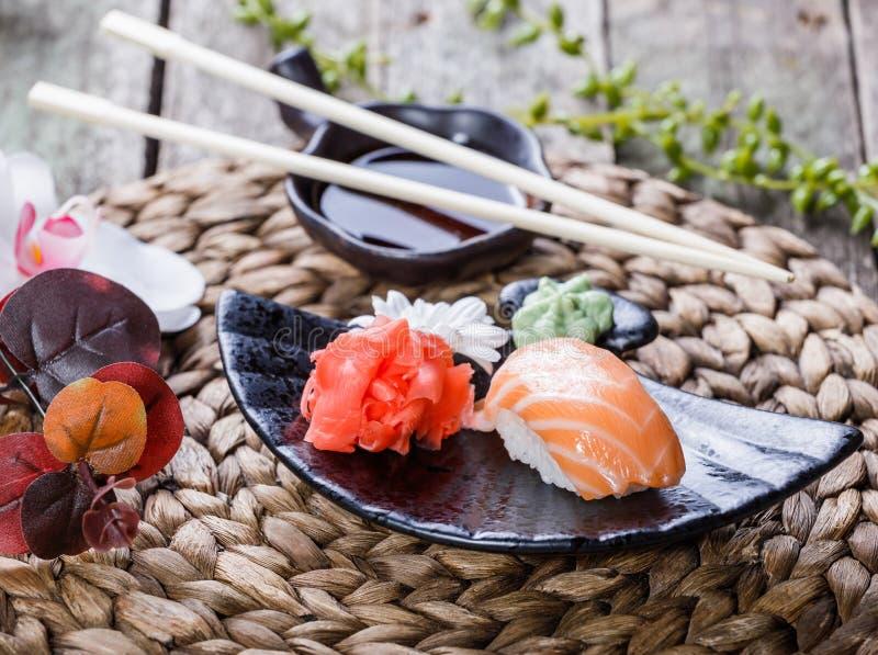 Nigiri determinado del sushi y rollos de sushi adornados con las flores en el fondo de bambú Cocina japonesa foto de archivo