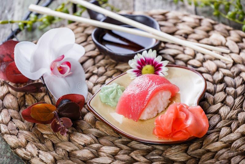 Nigiri determinado del sushi y rollos de sushi adornados con las flores en el fondo de bambú Cocina japonesa fotos de archivo