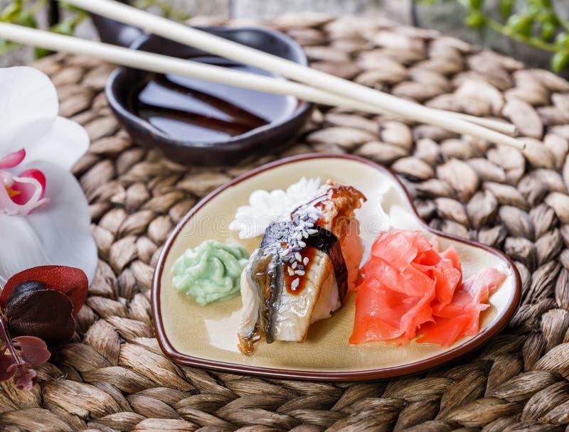 Nigiri determinado del sushi y rollos de sushi adornados con las flores en el fondo de bambú Cocina japonesa Foco selectivo imagenes de archivo