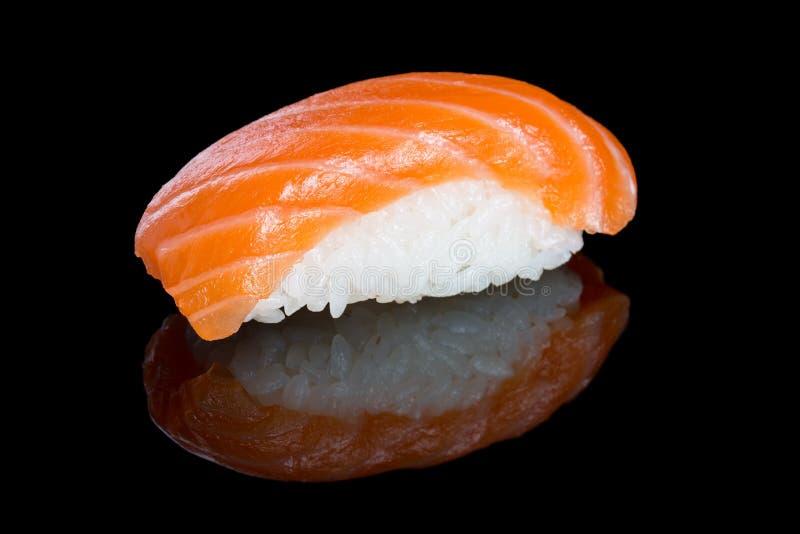 Nigiri do sushi com os salmões no fundo preto com reflexão Ja imagens de stock royalty free