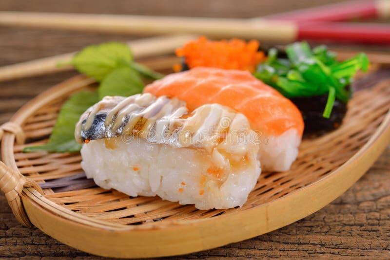 Nigirien och sashimien för sushi tjänade som den fastställda i bambuplatta på träbakgrund royaltyfri bild