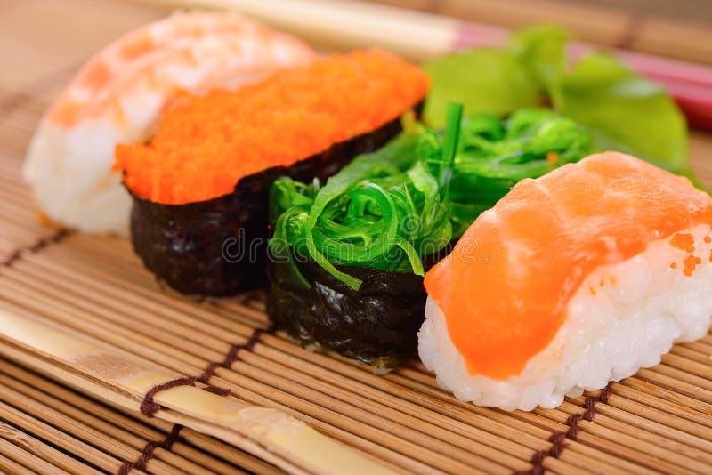 Nigirien och sashimien f?r sushi tj?nade som den fastst?llda p? matta pinnar royaltyfria foton
