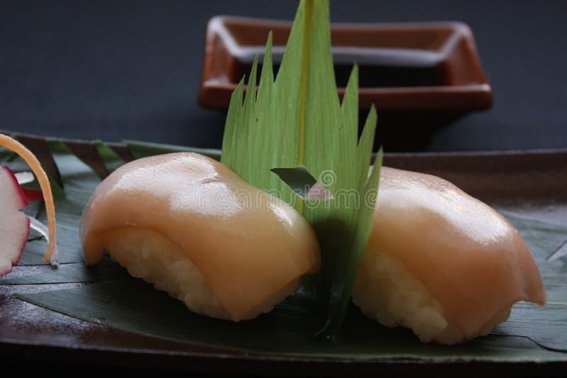 Nigirisushi met garnalen en tonijnvissen op het gastronomische platting op zwarte achtergrond stock afbeelding
