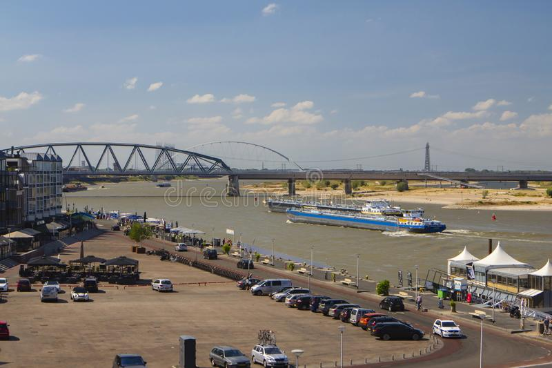 The river `Waal` at Nijmegen, Gelderland, the Netherlands. View of the Waalkade and the railway bridge over the Waal. De Waal is an important river for inland royalty free stock images